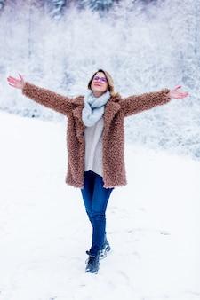 Belle fille en manteau dans une forêt de neige