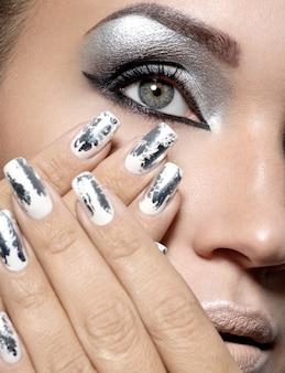 Belle fille avec le maquillage argenté et les ongles en métal.