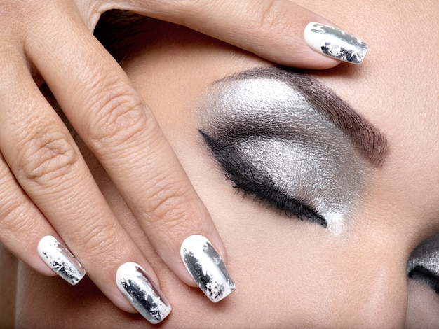 Belle fille avec le maquillage argenté des yeux et des ongles en métal.