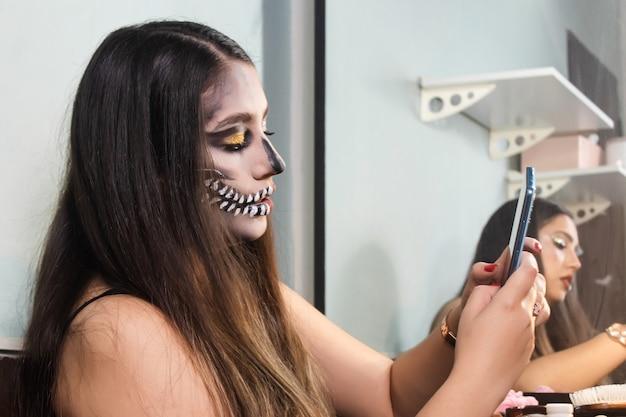 Belle fille avec le maquillage de crâne d'halloween à l'aide de son téléphone intelligent dans sa chambre