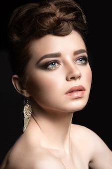 Belle fille avec maquillage lumineux et coiffure de soirée.