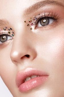 Belle fille avec un maquillage lumineux créatif avec des strass. beau visage.