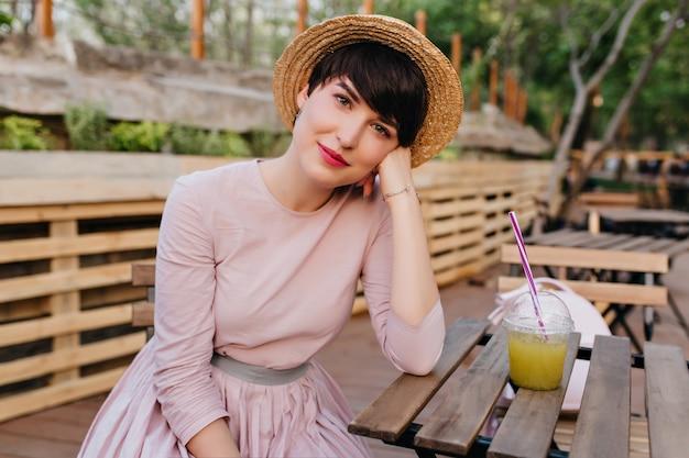 Belle fille avec un maquillage nude assis à la table en bois étayant le visage avec la main