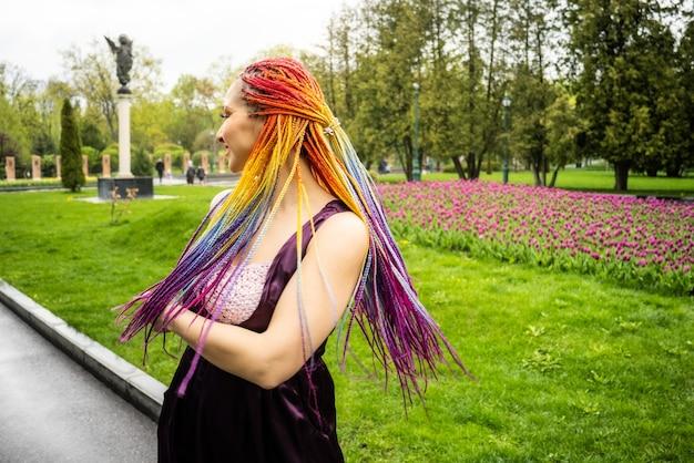 Une belle fille avec un maquillage pailleté multicolore et des tresses africaines lumineuses dans une robe en satin violet. elle sourit gentiment et se réjouit de l'arrivée du printemps tant attendu dans un parc fleuri.