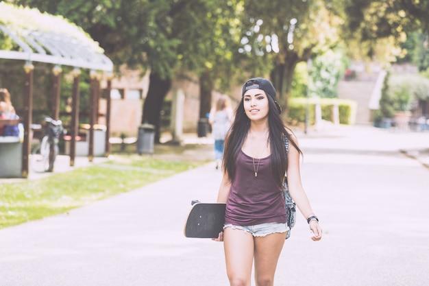 Belle fille marchant au parc tenant une planche à roulettes.
