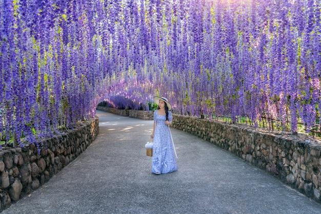 Belle fille marchant au tunnel de fleurs violettes à chiang rai, thaïlande