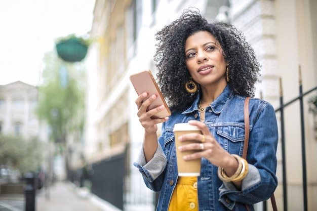 Belle fille marchant dans la rue, vérifiant son téléphone et buvant un café