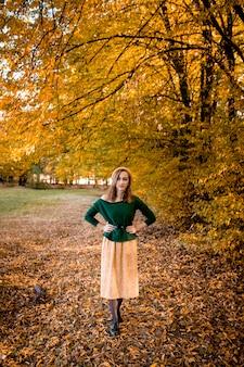 Belle fille marchant à l'extérieur en automne. jeune fille souriante recueille les feuilles jaunes à l'automne. jeune femme appréciant le temps d'automne.