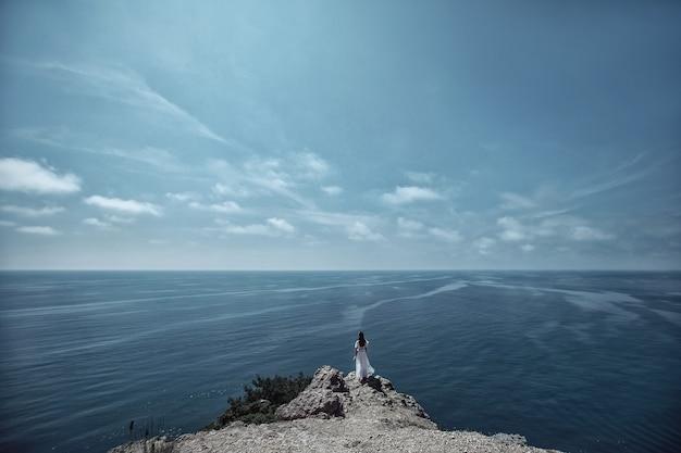 Une belle fille, une mariée, dans une robe blanche, se tient à l'arrière d'un rocher