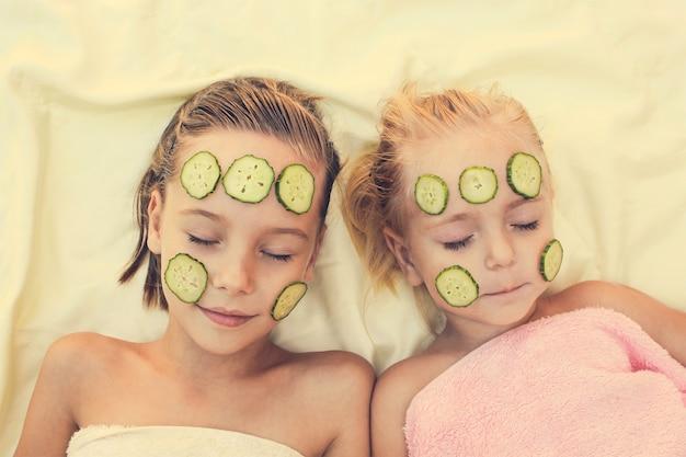 Belle fille avec un masque facial de concombre. image tonique
