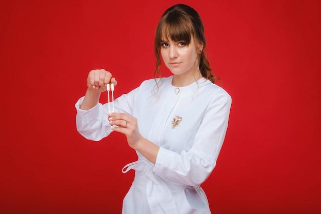 Belle fille médecin avec un diapason se dresse.