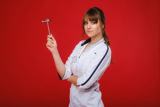 Une belle fille médecin tient un marteau réflexe et sourit à la caméra isolée sur fond rouge.