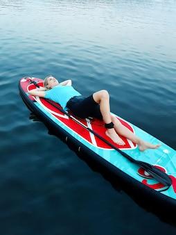 Une belle fille ment et se repose sur une planche de natation et tient ses mains derrière sa tête sur fond d'eau calme