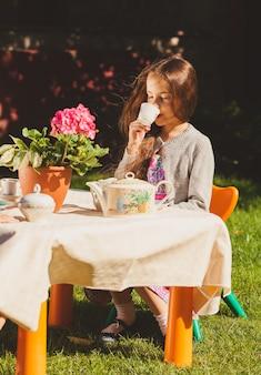 Belle fille mignonne buvant du thé à la table de jouets dans la cour