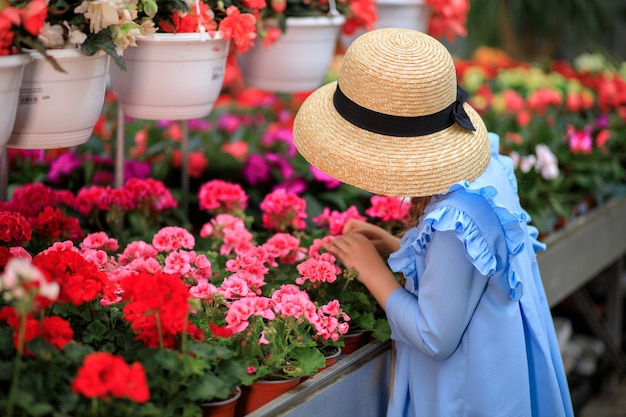 Belle fille mignonne dans un chapeau de paille dans une serre aux fleurs colorées