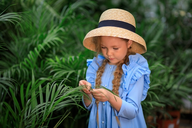 Belle fille mignonne dans un chapeau de paille dans une serre près des plantes vertes