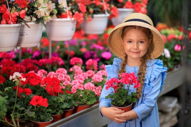 Belle fille mignonne dans un chapeau de paille tenant un pot de fleurs roses dans une serre avec des fleurs colorées