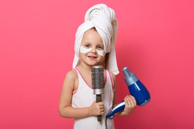 Belle fille mignonne avec sèche-cheveux bleu et peigne en mains