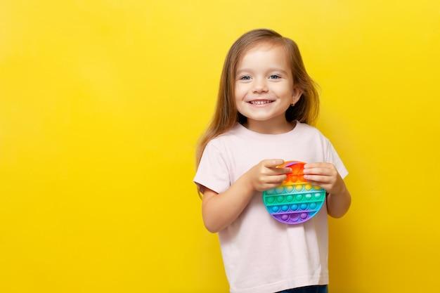 Une belle fille mignonne tient un jouet pop-it coloré dans ses mains et sourit sur fond jaune