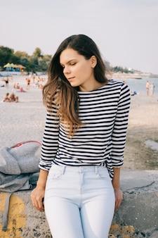Belle fille mince aux longs cheveux bruns dans un t-shirt à rayures et un jean sur la plage en été