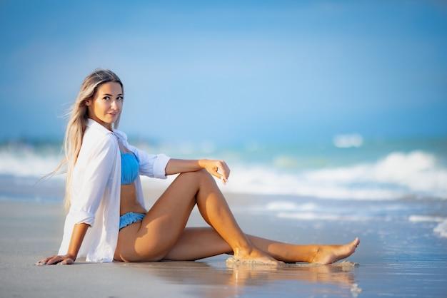 Une belle fille mince et bronzée dans un maillot de bain bleuâtre et une chemise blanche comme neige, est assise près du bord de l'eau de mer et regarde à l'horizon par une chaude journée d'été ensoleillée
