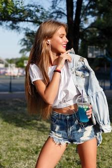 Belle fille mince buvant un cocktail. une fille adorable dans un costume en jean à la mode avec une longue coiffure et des lèvres rouges boit un portrait rafraîchissant de style de vie de limonade d'une fille heureuse. elle marche dans la rue
