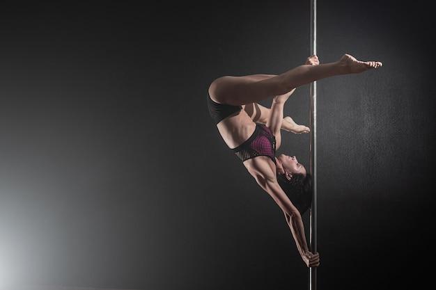 Belle fille mince avec pylône, danseur de pôle féminin dansant sur un fond noir