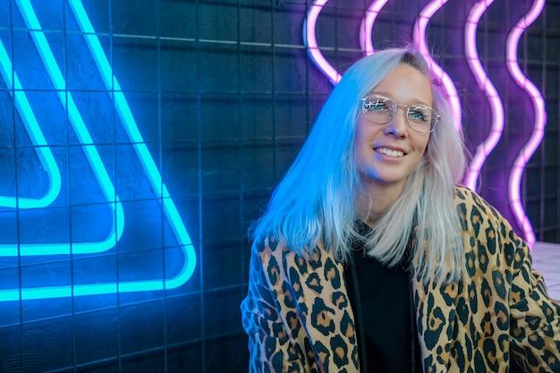 Belle fille à la mode assis dans un bar près du mur de néon