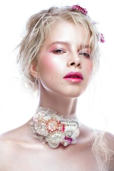 Belle fille de mode blonde avec des fleurs sur le cou et dans les cheveux, maquillage nu humide