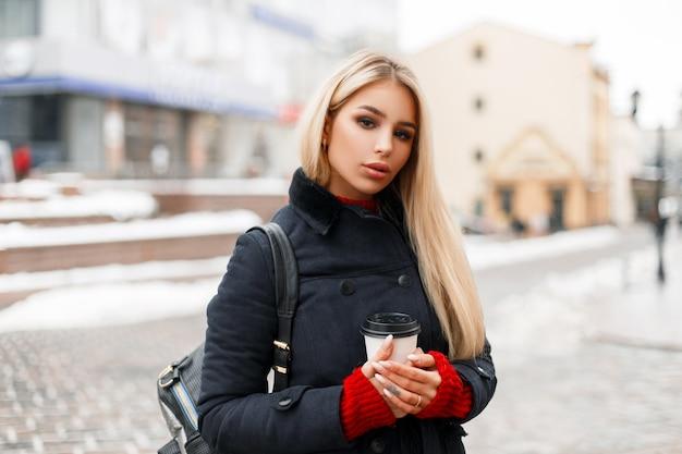 Belle fille à la mode avec du café dans un manteau d'hiver à la mode avec un sac marchant dans la ville