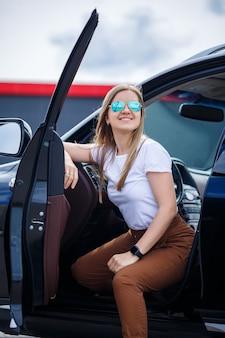Belle fille à la mode élégante assise dans le salon d'une voiture de classe affaires noire. jeune femme avec un sourire sur son visage.
