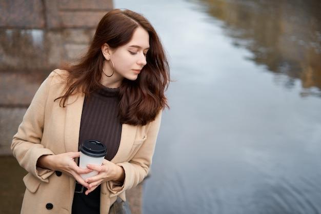 Belle fille à la mode élégante sérieuse tenant une tasse de café dans les mains marchant dans la rue