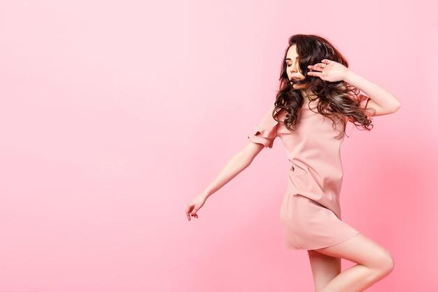 Belle fille à la mode avec de longs cheveux bouclés dans une robe rose en studio sur fond rose.