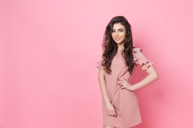 Belle fille à la mode avec de longs cheveux bouclés dans une robe rose en studio sur un rose.
