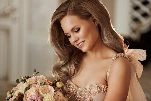 Belle fille modèle blonde heureuse avec un sourire charmant dans la robe élégante avec le bouquet de fleurs dans ses mains
