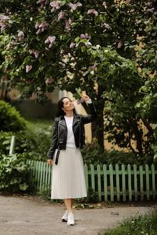 Belle fille modèle dans une jupe midi blanche et une veste en cuir noir posant près d'un lilas fleuri jeune femme brune en tenue de printemps posant à l'extérieur