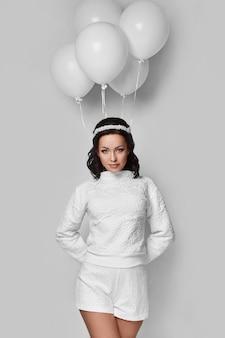 Belle fille modèle fashion avec des ballons blancs