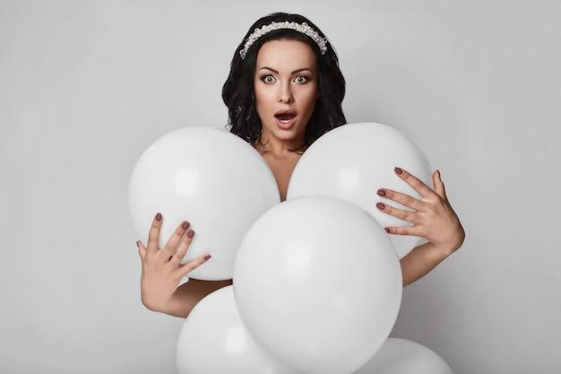 Belle fille modèle nue avec des ballons blancs