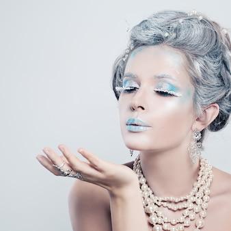 Belle fille modèle soufflant un baiser fashion portrait of winter woman profile