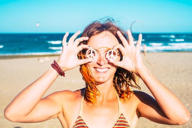 Belle fille montrant son symbole de la paix sur ses yeux tenus avec ses mains - femme en bikini à la plage souriant et regardant la caméra avec le soleil sur son visage