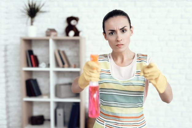 Belle fille nettoie la maison avec des détergents.