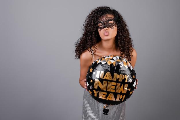 Belle fille noire avec ballon bonne année porter un masque de mascarade isolé sur gris