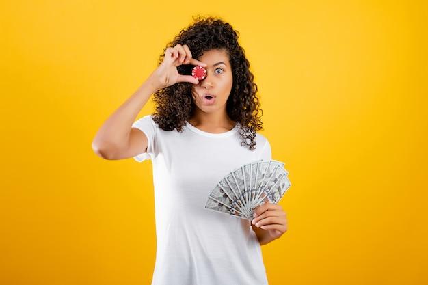 Belle fille noire avec jeton de poker du casino en ligne et de l'argent en dollars isolé sur jaune