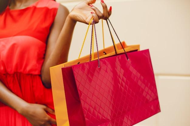 Belle fille noire avec des sacs dans une ville