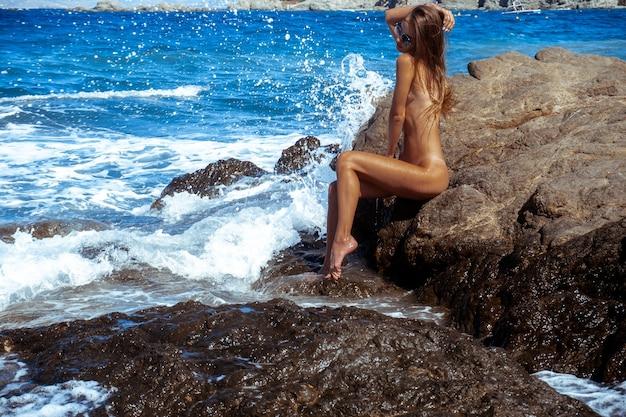 Belle fille nue sur un bord de mer rocheux