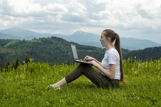 Belle fille avec un ordinateur portable assis sur l'herbe verte