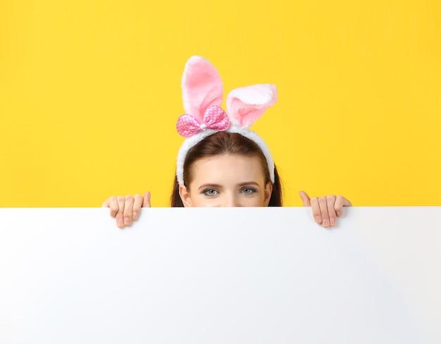 Belle fille avec des oreilles de lapin et une bannière vierge sur une surface de couleur