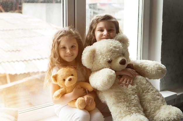 Une belle fille avec un ours en peluche un enfant avec un jouet le concept de passe-temps matinal de l'enfance
