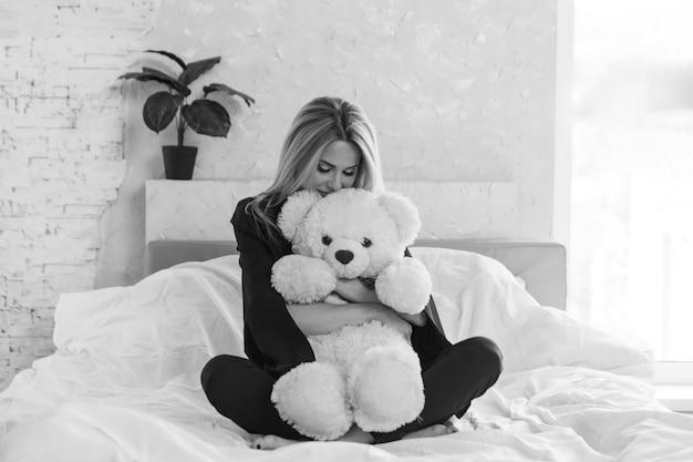 Une belle fille avec un ours en peluche une femme avec un jouet le concept de passe-temps matinal de l'enfance