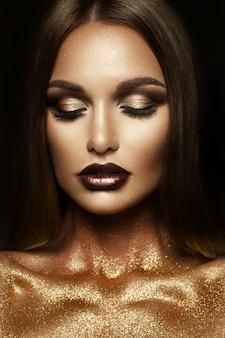 Belle fille avec des paillettes d'or sur son visage